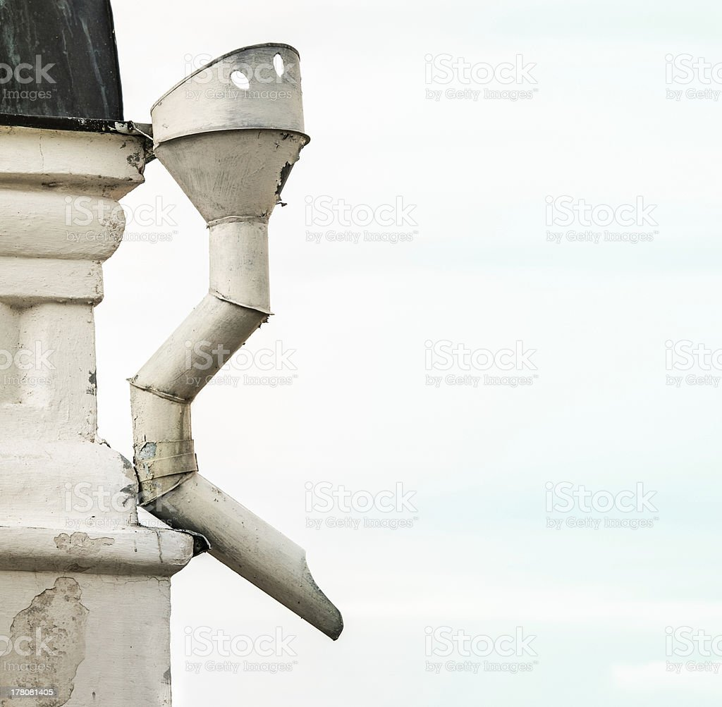 Metal sewer attached to corner of white building. stock photo