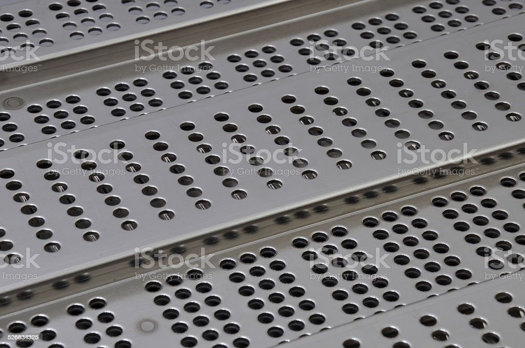 Metal sheet surface with holes stock photo