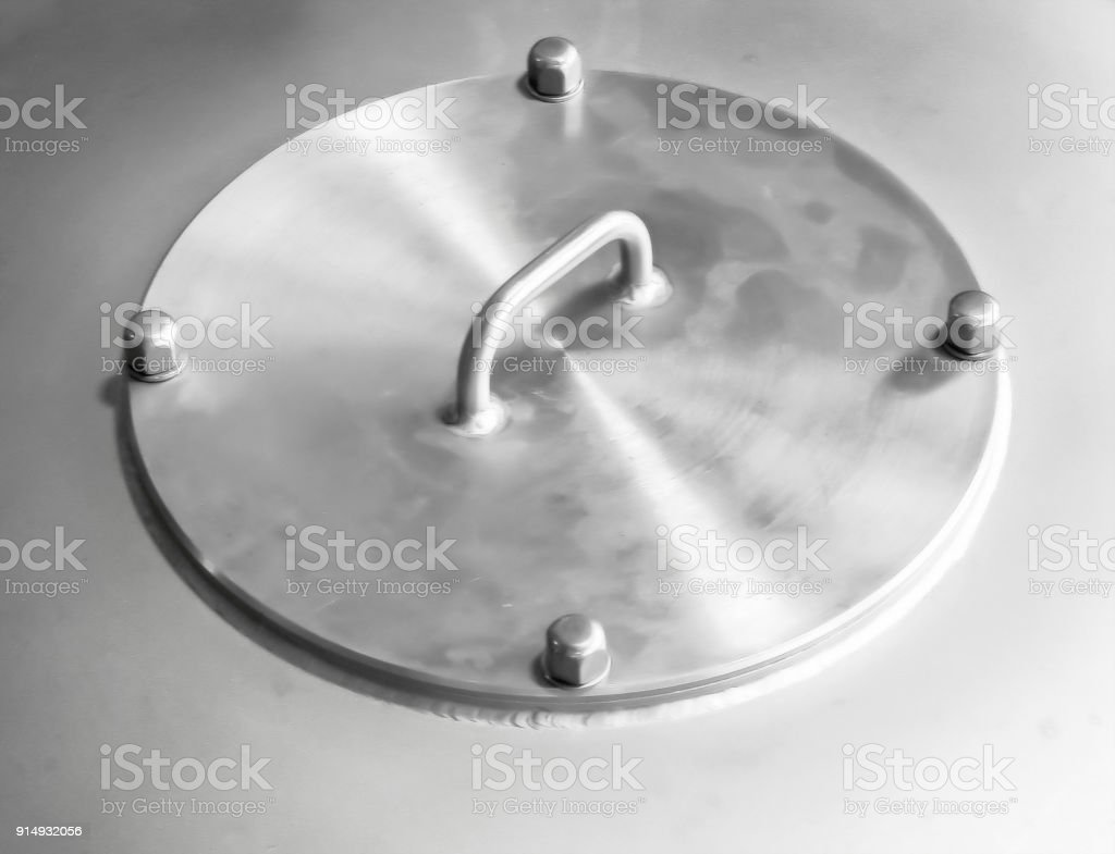 Metal shiny cover on the boiler with high air pressure in the factory food industry stock photo