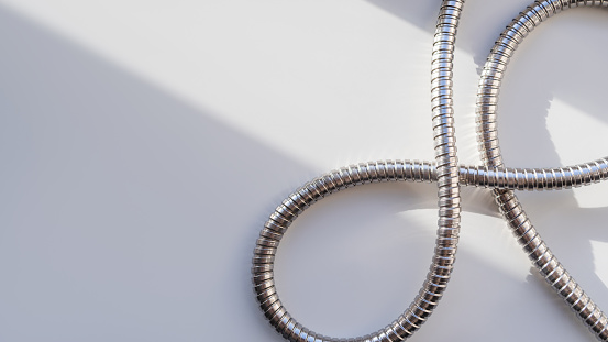 Metal shower hose on white background. Flexible chrome tube. Corrugated plumbing tube on geometrical banner with copy space on hard sunlight and shadow.