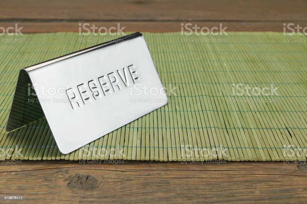 Metal Sign Reserve On The Restaurant Wood Table Background stock photo