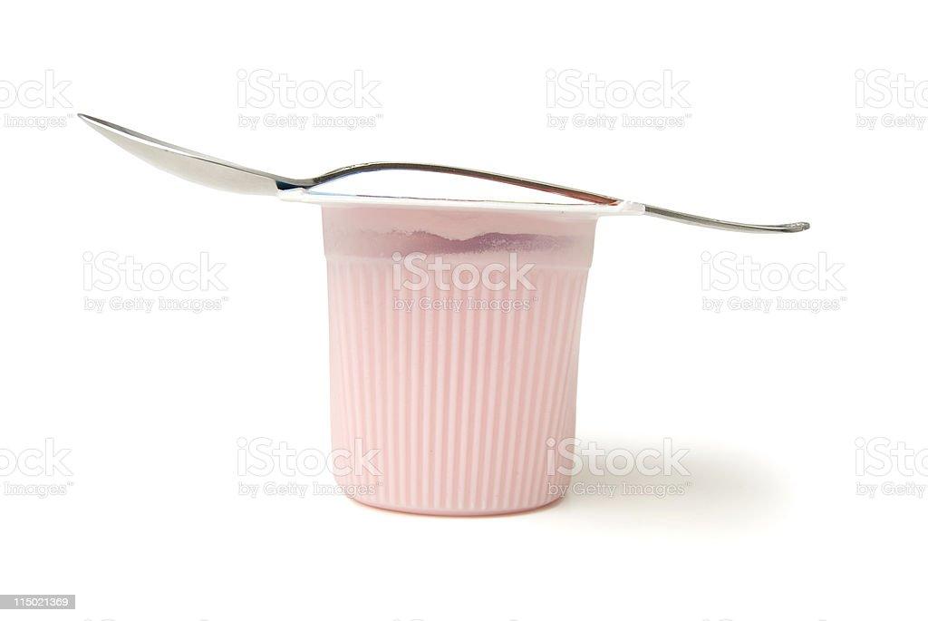 Metal spoon balancing on pink yogurt cup stock photo