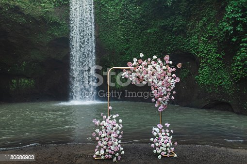 Metal square wedding arch decorated with pink and coral colored flowers anthurium, orchids and roses. Modern and unusual style, wedding outdoors on Tibumana waterfall Bali.