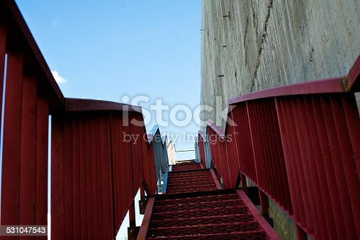 istock Metal stairs on the gray concrete wall 531047543
