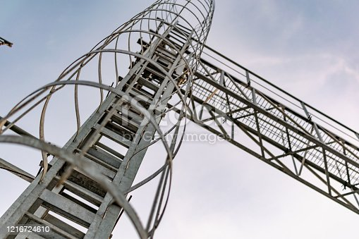 A metal structure made of thin but strong rings , chained together in a high tower stand for elevation to the top, covered with gray paint