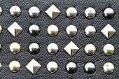 Metal studs on black leather background