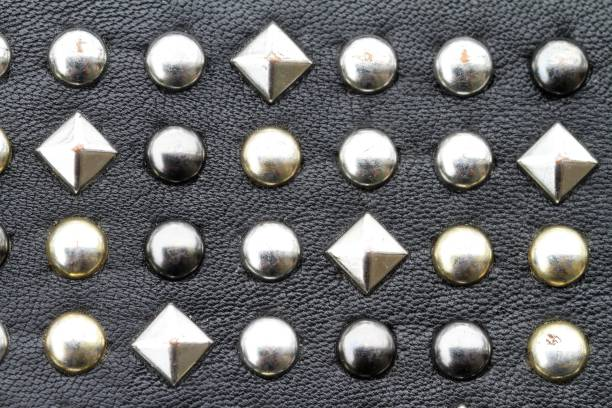 Metal studs on black leather background stock photo