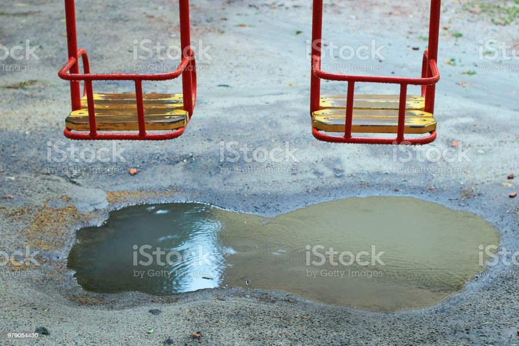 Metal swing with a wooden seat on a kids playground on a rainy day with a puddle under it stock photo