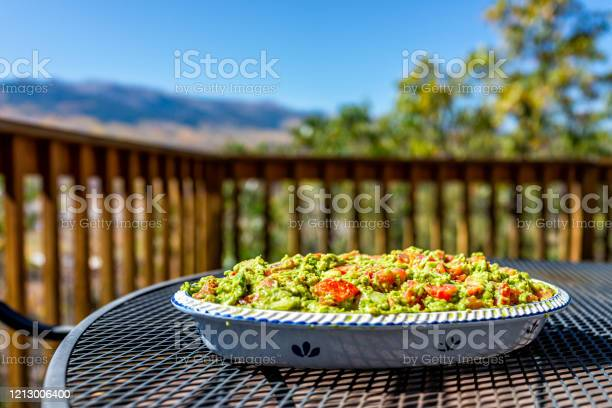 Photo of Metal table on deck mountain view and large big guacamole dish with tomatoes in serving tray with green avocado color for party platter
