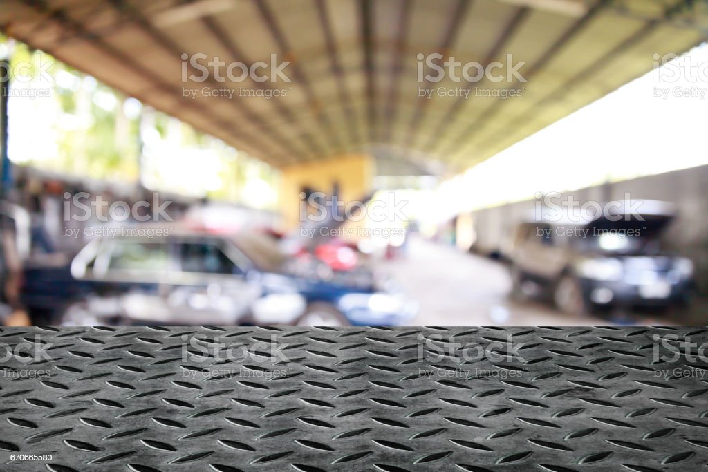 Metal table on garage background. - Photo