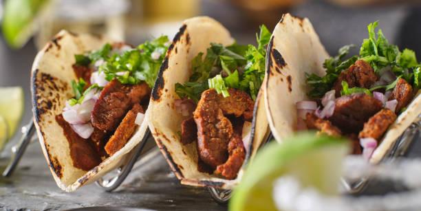 metal taco holder with three mexican carne asada street-tacos stock photo