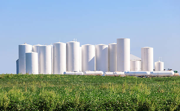 Metal tanks storing Anhydrous Ammonia Rural scene showing large grouping of metal tanks used to store ammonia for farm usage. anhydrous stock pictures, royalty-free photos & images
