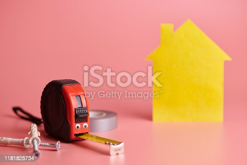 657926276istockphoto Metal tape measure funny concept. House renovation. Home repair and redecorated concept. Yellow house shaped figure on pink background. 1181825734