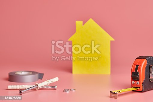 657926276 istock photo Metal tape measure funny concept. House renovation. Home repair and redecorated concept. Yellow house shaped figure on pink background. 1184628536