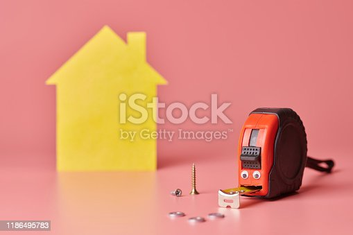 657926276 istock photo Metal tape measure funny concept. House renovation. Home repair and redecorated concept. Yellow house shaped figure on pink background. 1186495783