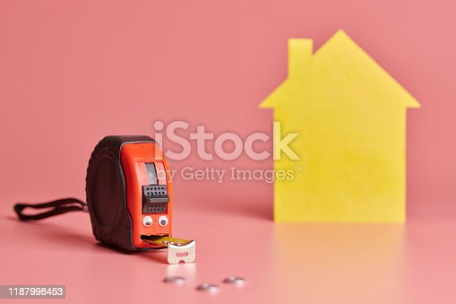 657926276 istock photo Metal tape measure funny concept. House renovation. Home repair and redecorated concept. Yellow house shaped figure on pink background. 1187998453