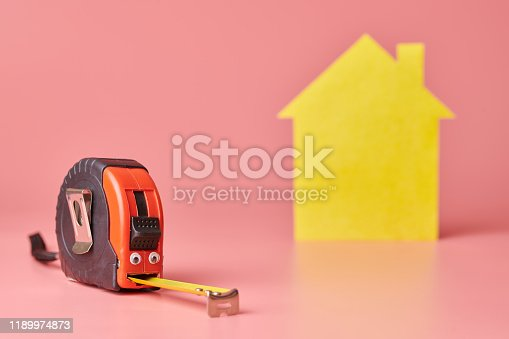 657926276 istock photo Metal tape measure funny concept. House renovation. Home repair and redecorated concept. Yellow house shaped figure on pink background. 1189974873