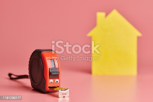 657926276 istock photo Metal tape measure funny concept. House renovation. Home repair and redecorated concept. Yellow house shaped figure on pink background. 1191230177