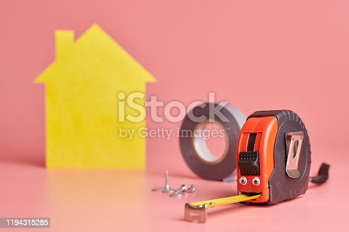 657926276 istock photo Metal tape measure funny concept. House renovation. Home repair and redecorated concept. Yellow house shaped figure on pink background. 1194315285