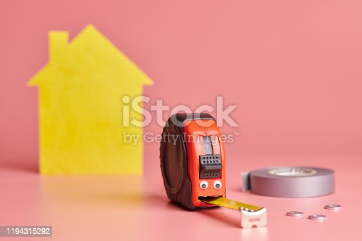 657926276 istock photo Metal tape measure funny concept. House renovation. Home repair and redecorated concept. Yellow house shaped figure on pink background. 1194315292