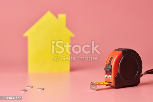 657926276 istock photo Metal tape measure funny concept. House renovation. Home repair and redecorated concept. Yellow house shaped figure on pink background. 1254031877