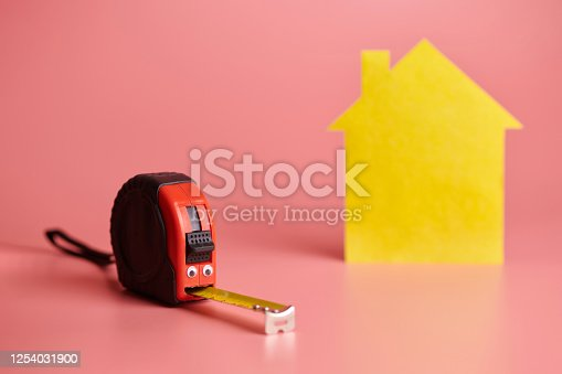 657926276 istock photo Metal tape measure funny concept. House renovation. Home repair and redecorated concept. Yellow house shaped figure on pink background. 1254031900