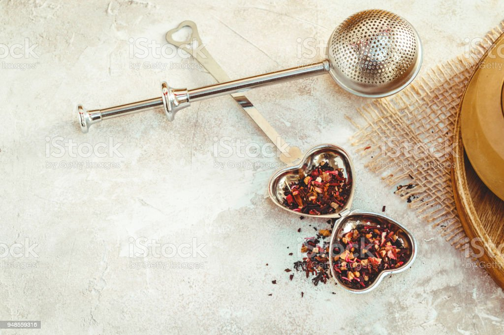 Metal tea infuser with leaves. Composition with tea accessories on a white background stock photo