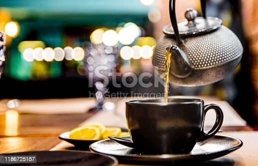 metal teapot pour black tea in black glass mug in cafe