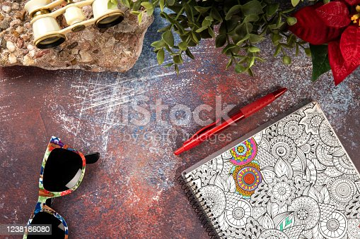 Old rusty metal texture for desk with a stone base, binoculars, sunglasses, notebook, pen and flower plants