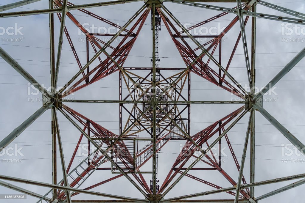 Metal tower power line bottom view against the sky