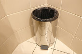 Metal trash can without cover with the package. Garbage collection in the bathroom at home or in the office. Open trash can in the toilet.