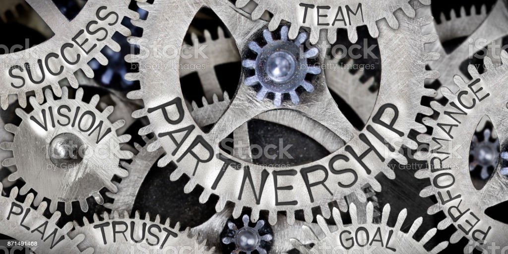 Metal Wheel Concept Macro photo of tooth wheel mechanism with Partnership related words imprinted on metal surface Partnership - Teamwork Stock Photo