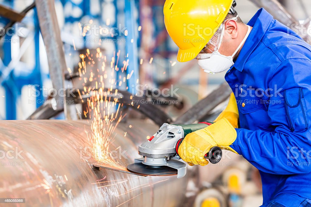 Metal worker in factory grinding metal of pipeline stock photo
