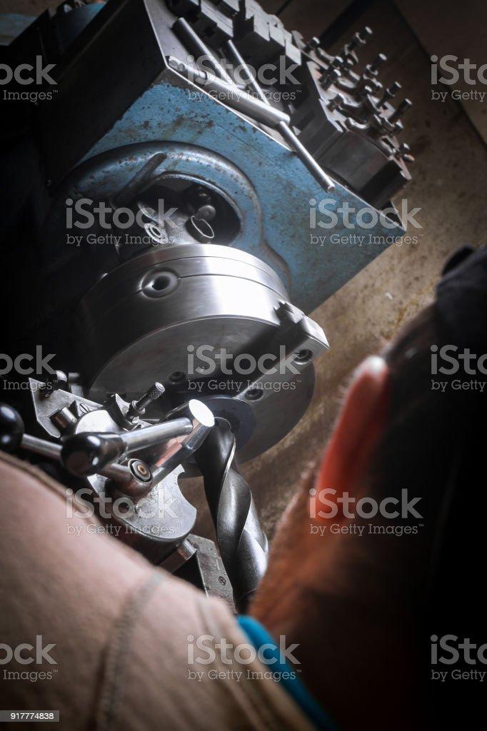Metal worker shaping metal on lathe machine stock photo