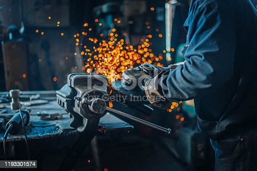 Industrial metal worker use the grinder in factory