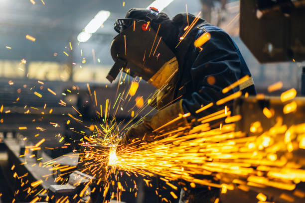 Metal worker using a grinder Metal worker using a grinder manufacturing stock pictures, royalty-free photos & images