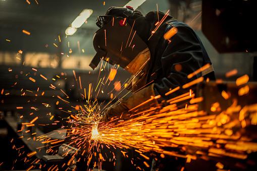 Metal worker using a grinder