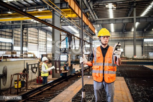 Metal worker using a remote controller to operate a crane in a factory.