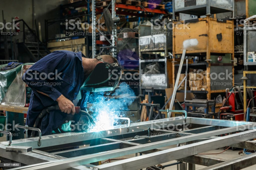Metal Worker Welding In Factory stock photo