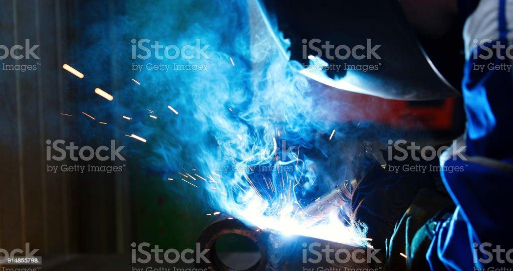 Metal worker welding with torch in metal industry factory