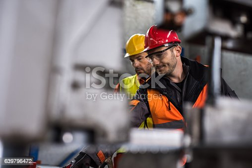 Two manual workers standing in a aluminum mill and working together. Focus is on man with red hardhat.