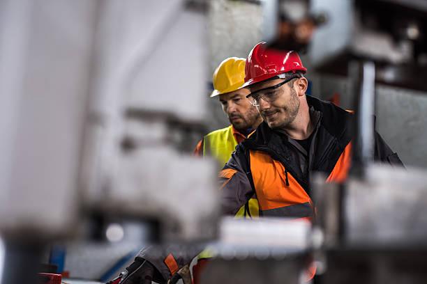 metalowcy współpracujący podczas pracy w aluminiowej fabryce. - kask ochronny odzież ochronna zdjęcia i obrazy z banku zdjęć