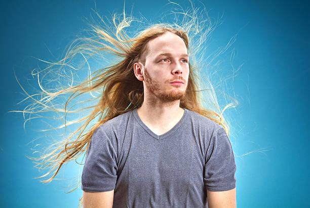 metalhead dude with long hair blowing in the wind - lang haar stockfoto's en -beelden