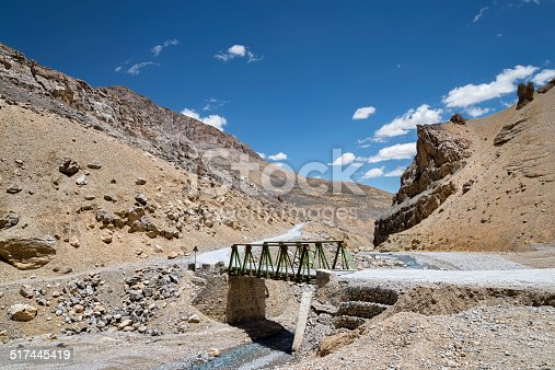 Metall construction bridge across river in mountains