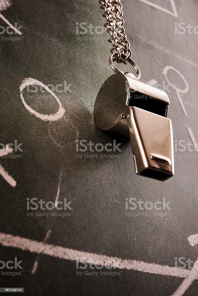 A metallic coach whistle with blackboard background stock photo