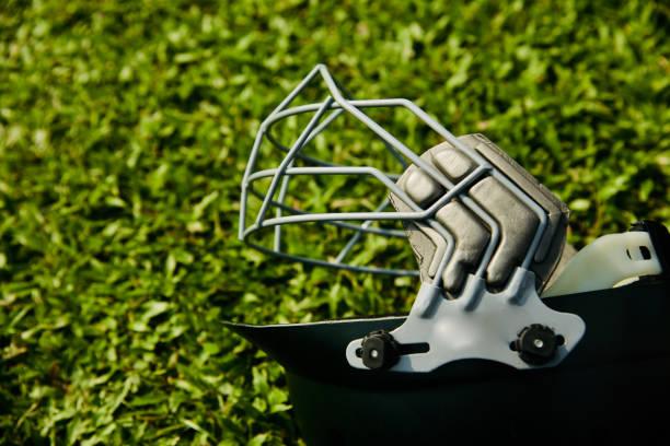 A metallic cricket helmet on green grass stock photo