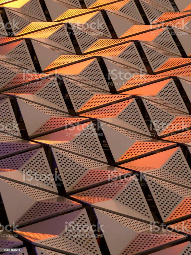 metallic geometric architectural cladding or panels in copper and gold colours with repeating angular pattern stock photo