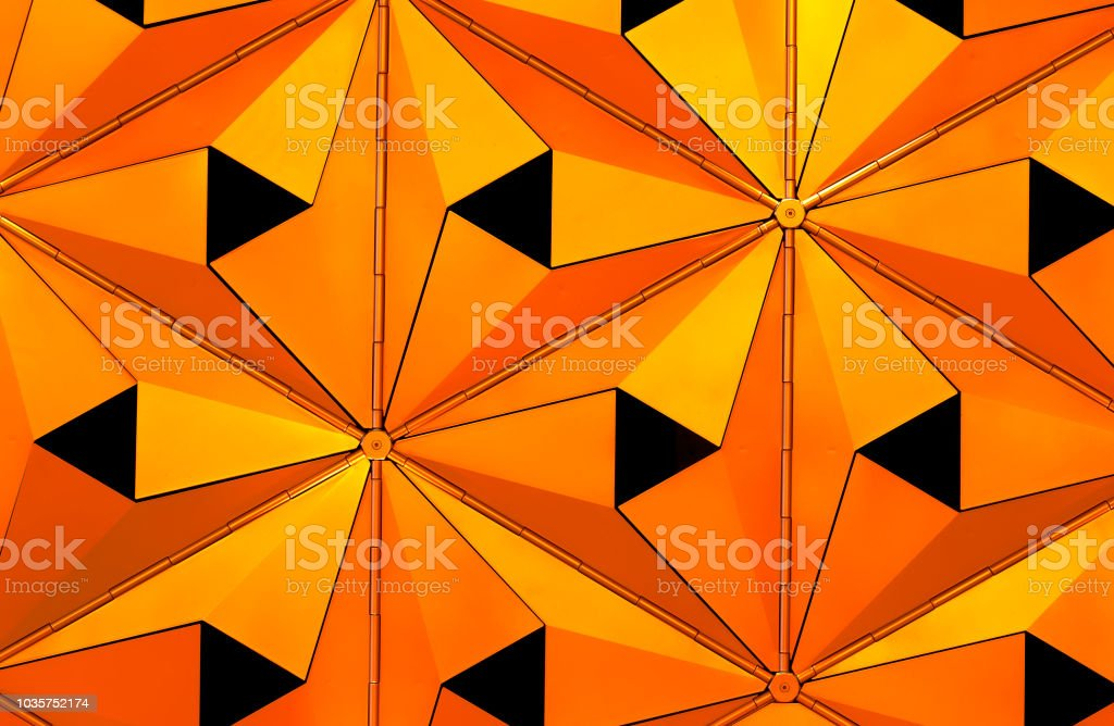 metallic geometric cladding or panels in copper and gold colors with repeating angular pattern stock photo