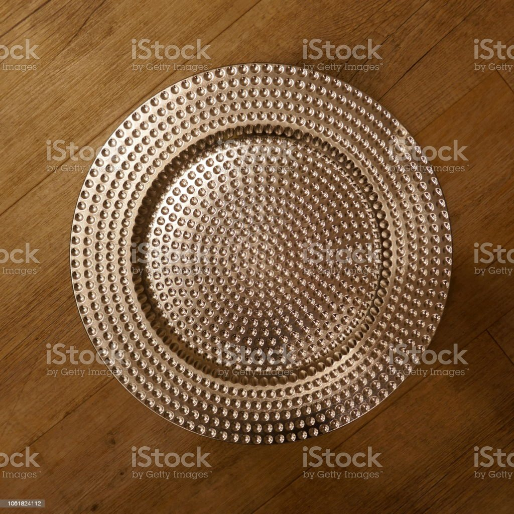 Metallic  glistening plate, isolated on wooden  background.Top view. stock photo