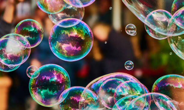 metallic glowing colorful soap bubble in the air in front of a blurry abstract background - saturated color stock pictures, royalty-free photos & images